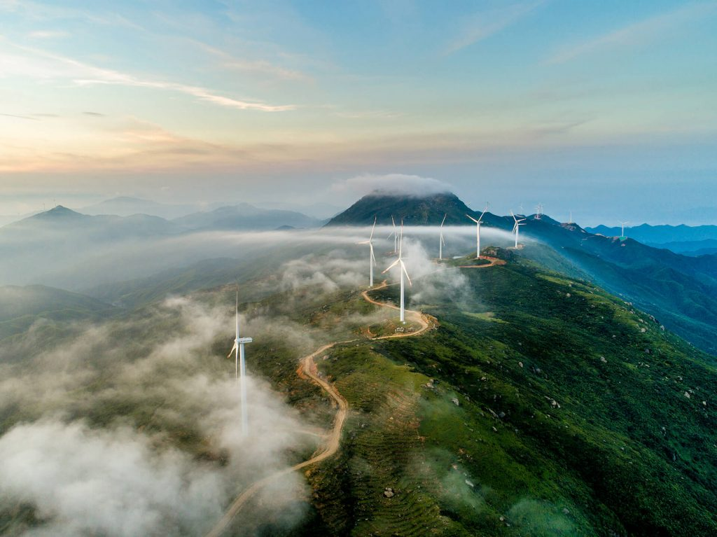 aerial photograph of wind farm with mountain in background
