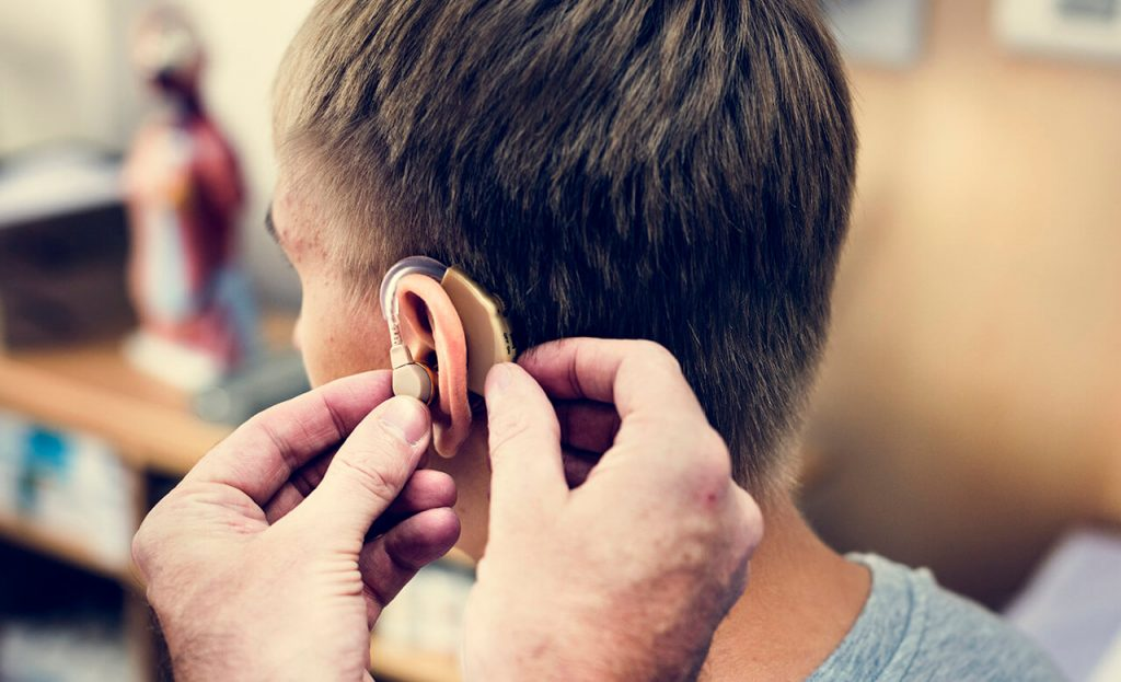 A man having his ears checked and hearing aid fitted